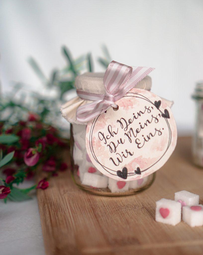 Hochzeit-Mitbringsel Zuckerherzen mit roten Blumen