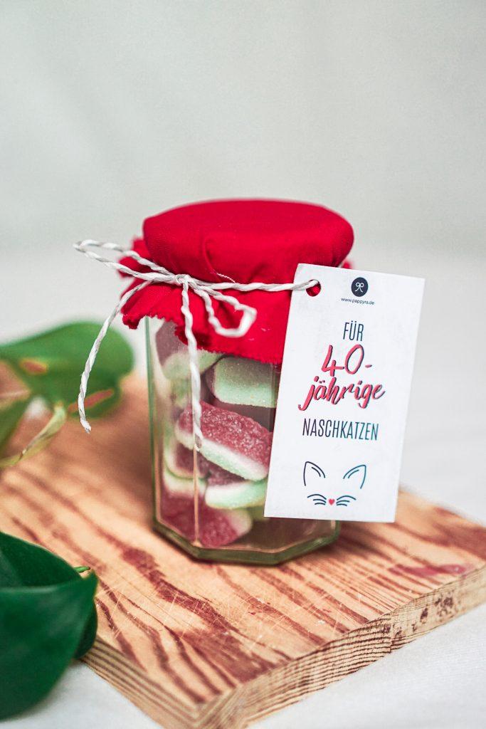 Gummibärchen im Einwegglas mit Geburtstags-Geschenkanhänger für einen runden Geburtstagstag