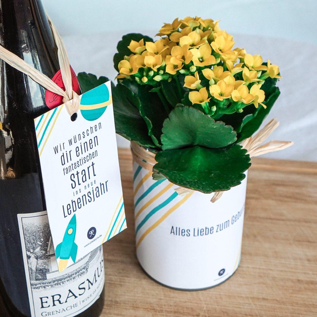 Weinflasche mit Geschenkanhänger und gelben Blumen,