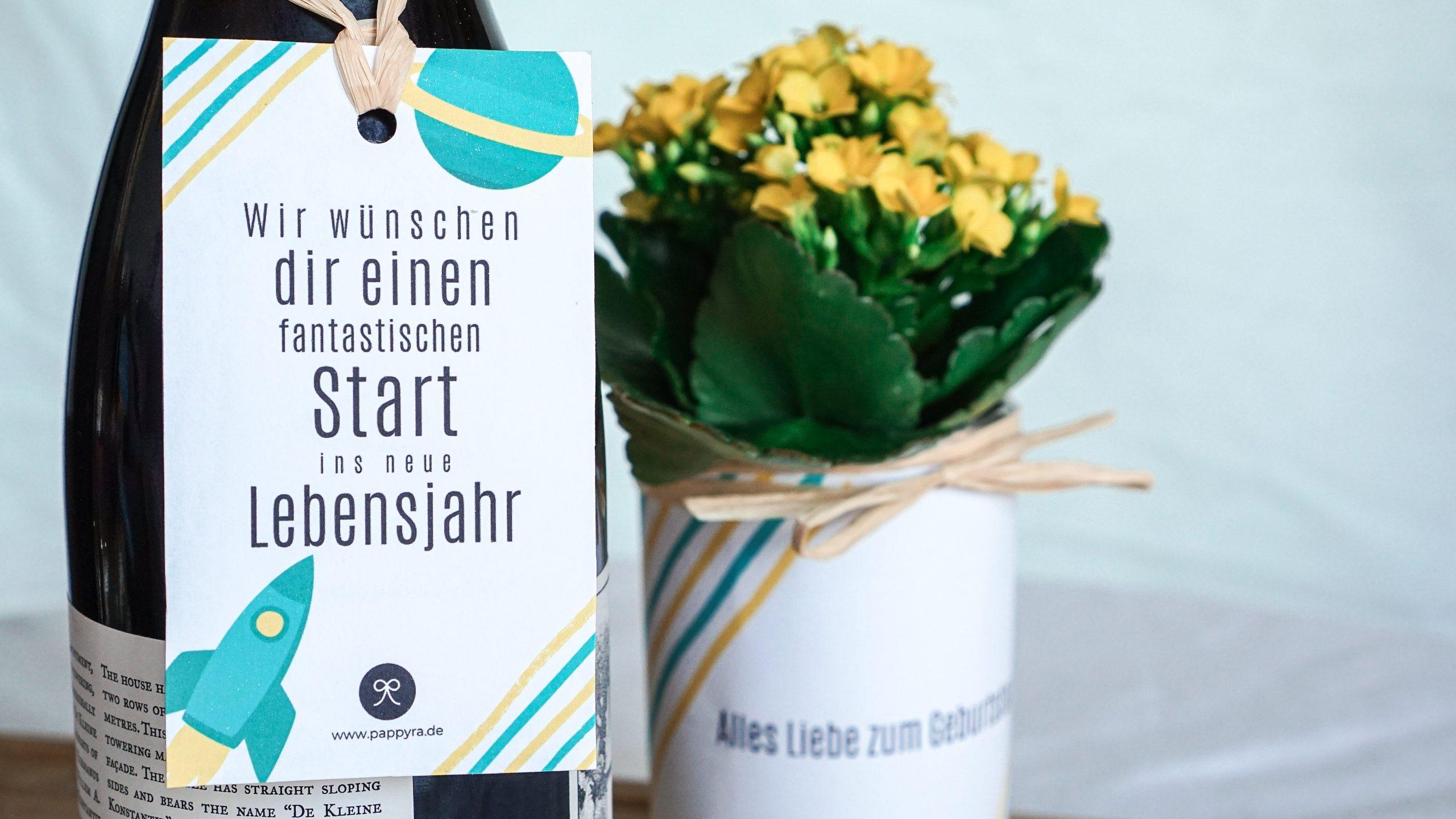 Weinflasche mit Geschenkanhänger und Blumen.